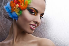 Woman with dramatic makeup and feather headdress  Stock Images