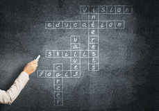 Woman draw crossword. Studying concept with crossword drawn on blackboard Stock Photos