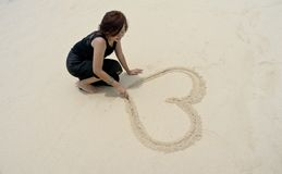 Woman draw love shape. Photograph of a beautiful woman draw love shape on beach during holiday Stock Photography