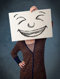 Woman with drawed smiley face on a paper in front of her head. Young woman holding a paper with a drawed smiley face on it in front of her head Royalty Free Stock Images