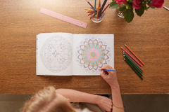 Woman drawing in adult colouring book. Overhead view of woman drawing in adult colouring book at home royalty free stock images