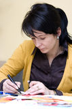 Woman drawing artwork. Attractive young woman seated at table drawing artwork Royalty Free Stock Photography