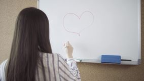 Woman drawing big heart on a whiteboard stock video footage