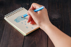 Woman drawing blue rain in notebook Stock Photography