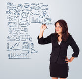 Woman drawing business scheme and icons on whiteboard. Young woman drawing business scheme and icons on whiteboard Royalty Free Stock Images