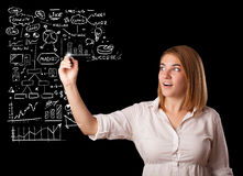 Woman drawing business scheme and icons on whiteboard Royalty Free Stock Photos