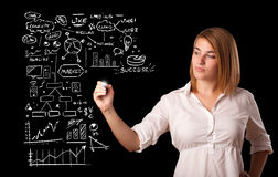 Woman drawing business scheme and icons on whiteboard Royalty Free Stock Photography