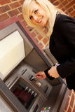 Woman drawing cash at an ATM Stock Images