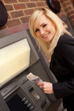 Woman drawing cash at an ATM Stock Photography