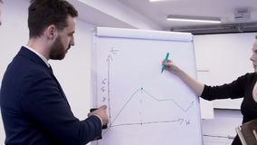 Woman is drawing chart on white board, which is discussed by business men. stock video footage