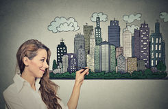 Woman drawing city skyline. Real estate development Stock Photo