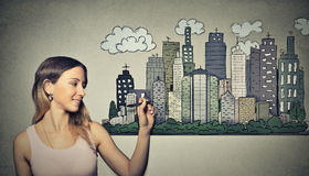Woman drawing city skyline. Real estate development Royalty Free Stock Photography