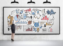 Woman drawing colorful icons on whiteboard. Side view of blond girl drawing sketches on whiteboard in room with concrete walls and floor. Concept of business Royalty Free Stock Image
