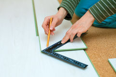 Woman drawing cut line. On laminate floorboard stock photography