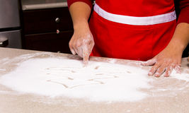 Woman drawing into flour Stock Photo