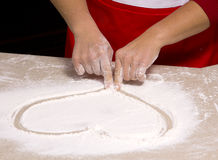Woman drawing into flour Royalty Free Stock Image