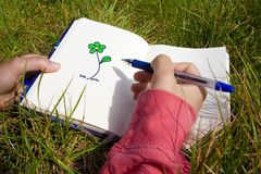 Woman drawing flowers. Young woman drawing flowers in the sketchbook Royalty Free Stock Photo