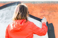 Woman drawing graffiti with spray paint from back Royalty Free Stock Photos