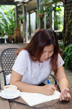 The woman is drawing. A happy Asian woman is writing on her diary in backyard garden Stock Image