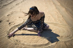 Woman drawing heart. Pretty young woman drawing heart on the sand Royalty Free Stock Image