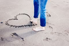 Woman drawing heart on beach sand with her foot. Royalty Free Stock Photo