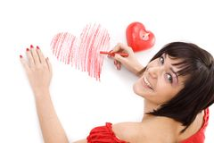 Woman drawing heart-shape. Beautiful young woman with wax crayon lying on floor and drawing heart-shape Royalty Free Stock Images