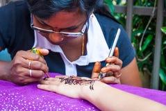 Woman drawing henna tattoo Stock Photo