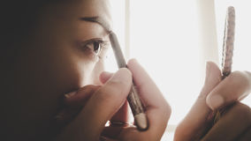 Woman drawing her eyebrow. Royalty Free Stock Photography