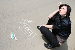 Woman drawing house. With chalk on the asphalt road and dreaming about it Royalty Free Stock Photography