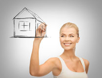 Woman drawing house on virtual screen Royalty Free Stock Photo