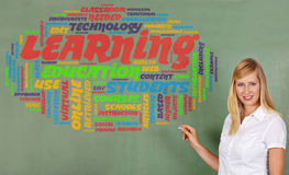 Woman drawing learning. Smiling woman drawing learning and education tag cloud on a chalkboard Royalty Free Stock Photos