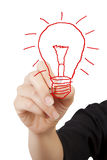 Woman drawing light bulb. Royalty Free Stock Photos