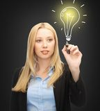 Woman drawing light bulb. Business, energy and environment concept - woman drawing light bulb on the virtual screen Royalty Free Stock Image