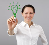 Woman drawing a light bulb Stock Images