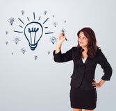Woman drawing light bulb on whiteboard Stock Photos