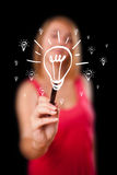 Woman drawing light bulb on whiteboard Stock Photography