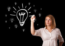 Woman drawing light bulb on whiteboard Stock Photo
