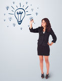 Woman drawing light bulb on whiteboard. Young woman drawing light bulb on whiteboard Royalty Free Stock Image