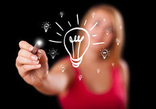 Woman drawing light bulb on whiteboard Stock Image
