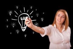 Woman drawing light bulb on whiteboard Royalty Free Stock Photos