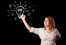Woman drawing light bulb on whiteboard Royalty Free Stock Images