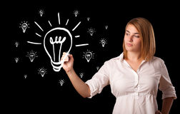Woman drawing light bulb on whiteboard Royalty Free Stock Photo
