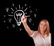 Woman drawing light bulb on whiteboard Stock Images