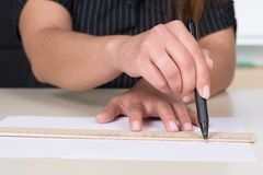 Woman is drawing a line with pen and ruler Royalty Free Stock Photo