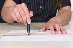 Woman is drawing a line with pen and ruler Royalty Free Stock Images