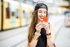 Woman drawing lips outdoors. Young stylish woman in black dress and hat drawing lips with lipstick standing outdoors no the tramstop stock images