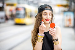 Woman drawing lips outdoors. Young stylish woman in black dress and hat drawing lips with lipstick standing outdoors no the tramstop royalty free stock image