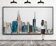 Woman drawing New York. Young businesswoman drawing a picture of New York city centre with colours in a frame, three lamps above. Back view. Concept of dreaming Stock Images