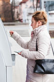 Woman drawing out money from ATM Stock Photo