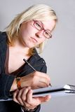 Woman drawing on pad of paper. Modern young blond woman taking notes/drawing on a notepad. Can be used as a business or artistic environment Royalty Free Stock Photography